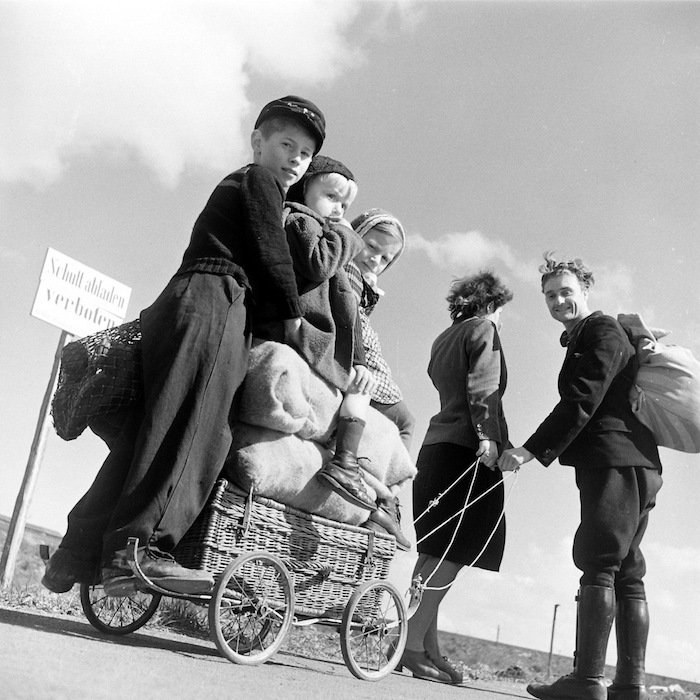 Margaret Bourke-White, Couple pulling a car loaded with children, Germany, 1945, Vintage gelatin silver print, Courtesy Syracuse University Library © Time & Life / Getty Images
